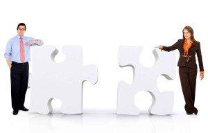 business partnership of a couple of businesspeople leaning on puzzle pieces isolated over a white background